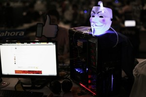 "A Guy Fawkes mask is seen on a computer as a man surfs the web during a ""Campus Party"" Internet users gathering in Sao Paulo"
