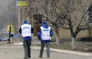 Members of the OSCE walk past a burning building after a shelling by pro-Russian rebels of a residential sector in Mariupol, eastern Ukraine