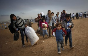 File photo of Kurdish Syrian refugees carrying their belongings after crossing the Turkish-Syrian border near the southeastern town of Suruc in Sanliurfa province