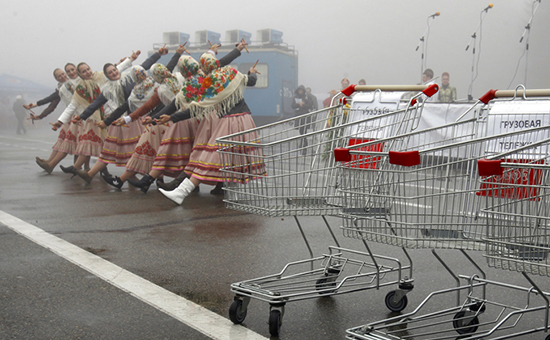 Women dressed in folk costumes dance behind empty shopping trolleys during a food fair in Stavropol
