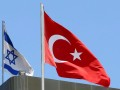 A Turkish flag flutters atop the Turkish embassy as an Israeli flag is seen nearby, in Tel Aviv, Israel