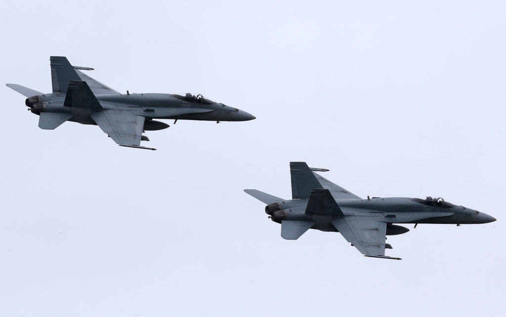 In this May 31, 2014, file photo, two Royal Canadian Air Force F-18 Hornet jets fly over Romania. Canada's new government has decided to stop airstrikes against Islamic State in the Middle East. (CNS photo/Mircea Rosca, EPA) See CANADA-ISIS-AIRSTRIKES Nov. 13, 2015.
